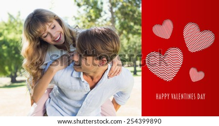Man giving his pretty girlfriend a piggy back in the park smiling at each other against cute valentines message - stock photo