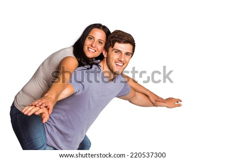 Man giving his pretty girlfriend a piggy back on white background - stock photo