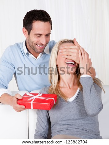 Man giving his wife a surprise gift at home - stock photo