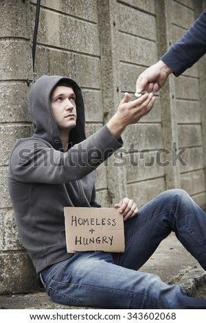 Man Giving Money To Beggar On Street