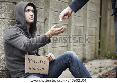 Man Giving Money To Beggar On Street - stock photo