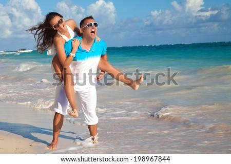 Man giving piggyback ride to girlfriend at the sandy Caribbean beach - stock photo