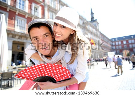 Man giving piggyback ride to girlfriend in Madrid - stock photo