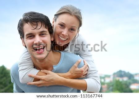 Man giving piggyback ride to girlfriend outside - stock photo
