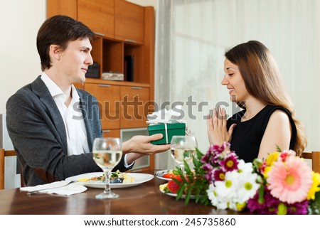 Man giving present to young woman during romantic dinner with champagne in home
