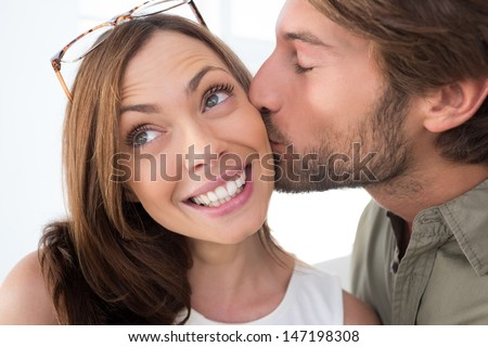 Man giving pretty woman kiss on the cheek as she is smiling - stock photo