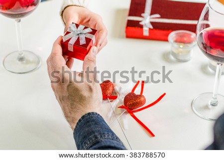Man giving small present during dinner - stock photo