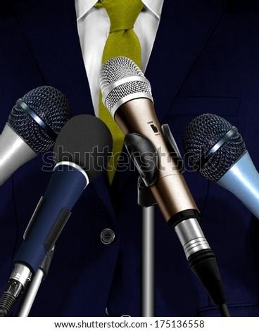 Man Giving Speech Using Microphones - stock photo