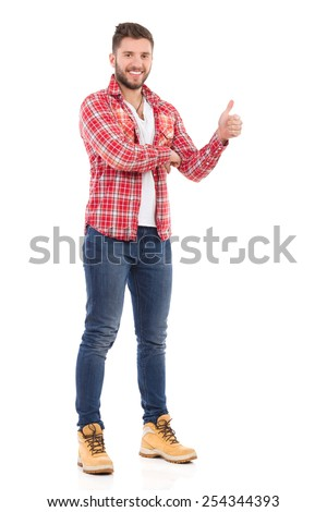 Man giving thumb up. Smiling young man in jeans and lumberjack shirt showing thumb up. Full length studio shot isolated on white.