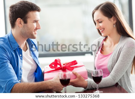 Man giving woman gift at cafe - stock photo