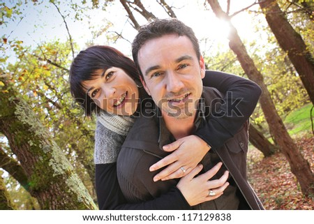 man giving woman piggy-back ride - stock photo