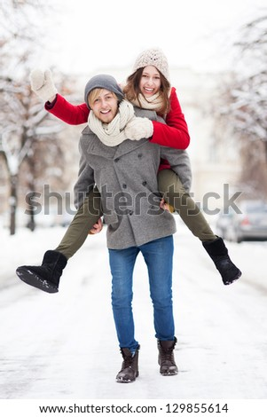 Man giving woman piggyback in winter setting - stock photo