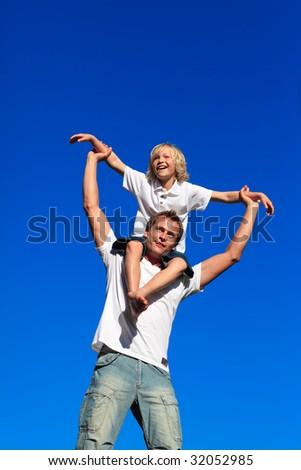 Man giving young boy piggyback ride outdoors smiling - stock photo
