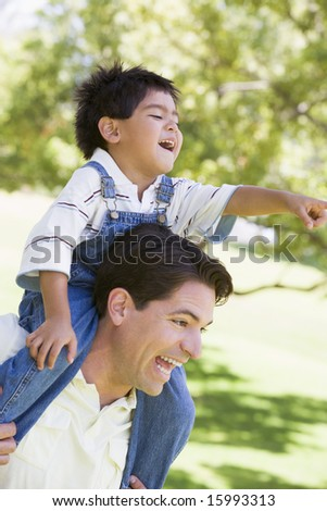 Man giving young boy shoulder ride outdoors smiling