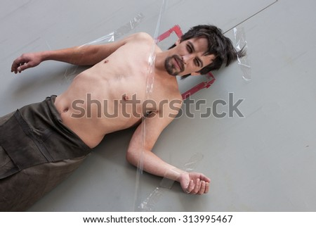 man glued to the wall with duct tape
