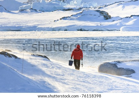Man goes fishing in a snowstorm. Antarctica - stock photo