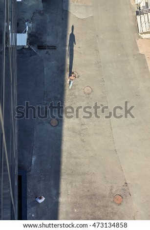 man goes on an asphalt road against buildings and cast a long shadow of man, silhouette of man in sunshine near building in shadow, top view, high resolution
