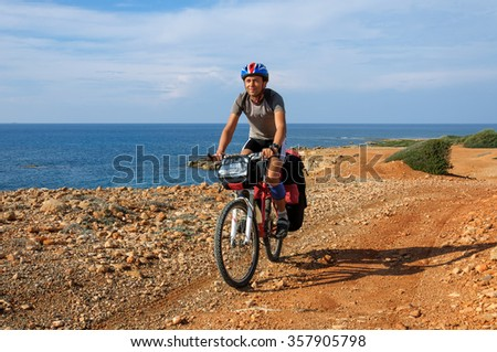 man goes  sandy beach on mountain bike with big backpack.  - stock photo