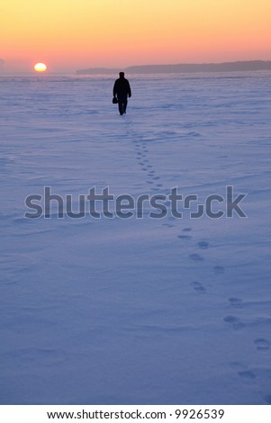 man goes through the snowy field