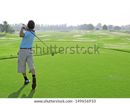 Man golf player with driver teeing-off from tee-box to ward, view from behind.  - stock photo