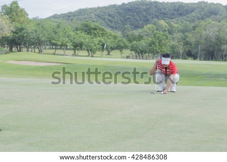 Man golfer put the golf ball and reading the green to judge the line of the putt - stock photo