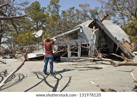 man grieving over house destroyed in flood. - stock photo