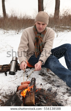 Man grilling sausages at campfire in winter forest