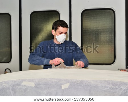 Man grinding car roof in a body shop. - stock photo