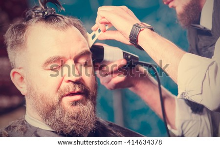 Man hairdresser cutting hair man with a beard and a clip on the head