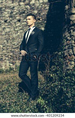 Man half face young handsome elegant model in suit with skinny necktie poses with hand in trouser pocket one leg backward outdoor on masonry background - stock photo