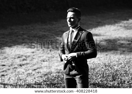 Man half face young handsome elegant model undoes buttons on suit coat with skinny necktie poses on landscape black and white on grey background - stock photo