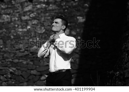 Man half face young handsome sensual model does up all buttons on shirt collar trousers outside black and white on masonry background  - stock photo