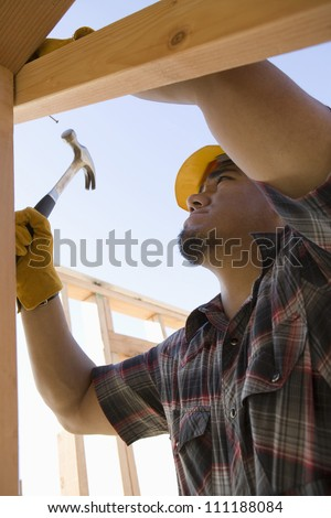Man hammering nail to wooden beam at construction site - stock photo