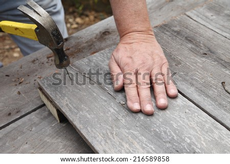 Man hammers old nail into weathered fence boards. - stock photo