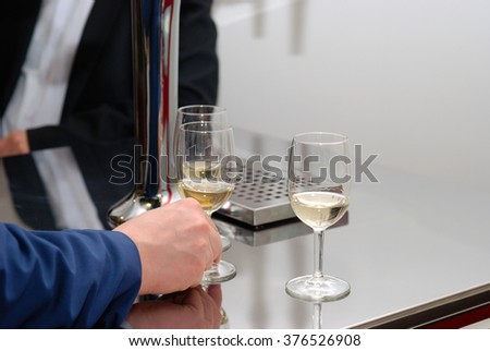 Man hand and three glasses of white wine on the metallic table. Degustation. - stock photo