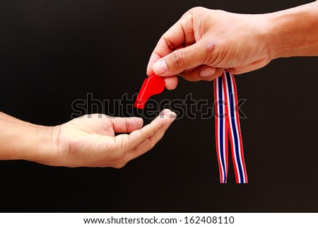 Man hand as action of put the red whistle  - stock photo