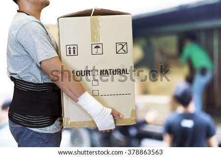Man hand bandage, lift heavy carton wearing support belt for protect his back, blurred background of worker lift cartons