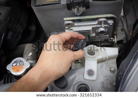 man hand check and fill water in cooling system Thailand Eco Car 1600cc with open hood show parts in side. - stock photo