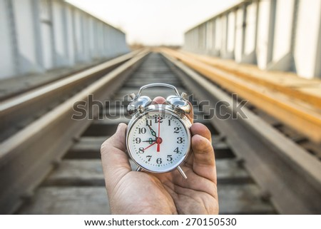 Man hand hold alarm clock Male look at watch outdoor alone against wooden sleeper between metal rusty rails and fence of bridge against sky background Idea symbol of tourism travel Too late train left