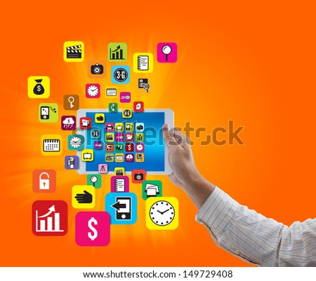 Man hand hold digital tablet with colorful application and social media icon on orange background - stock photo
