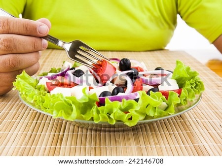 man hand hold fork with red fresh tomatoes under glass transparent plate with greek healthy salad with green leaf round onion black olive cheese Male no face unrecognizable person eating health food - stock photo