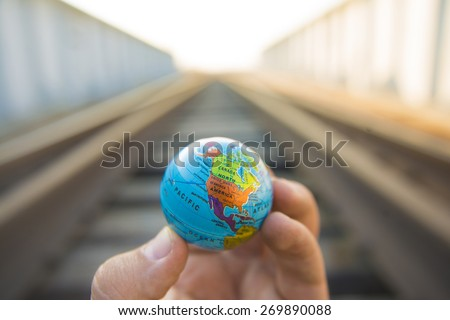 Man hand hold in hand Circle globe against metal railway in perspective road transportation against summer sunset light sky Idea symbol concept of logistic transport Future development of planet Earth - stock photo