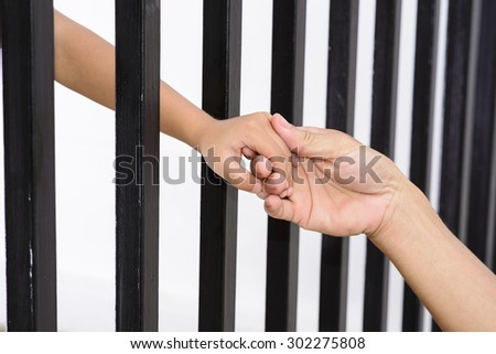 Man hand hold kid hand from black grid