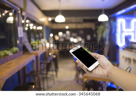 Man hand hold Smart Phone,Cell phone, Mobile phone, on the coffee shop background. - stock photo