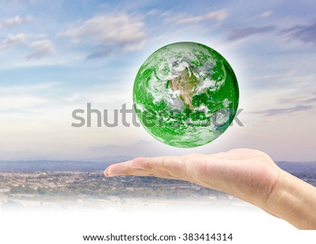 Man hand hold world with city background: Elements of this image furnished by NASA