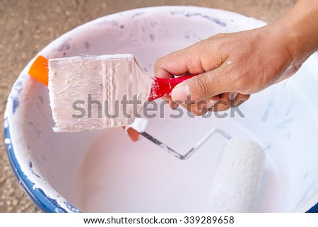 Man hand holder with paint brush and white paint