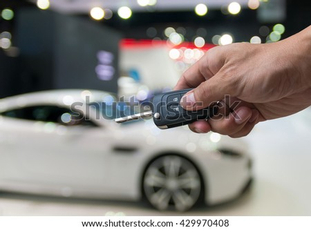Man hand holding a car key remote on photo blurred of car, technology safety transportation concept