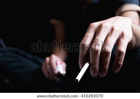 Man hand holding a cigarette with copy space. Concept of tobacco day. - stock photo