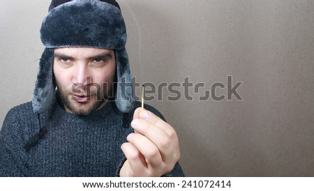 Man hand holding a match. Firewood, heating concept. Russian style man.