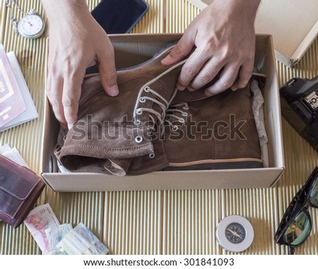 Man hand holding a pair de boots of the box. Variaty of utensils to travel. Reflection on sunglasses of woman saying goodbye.